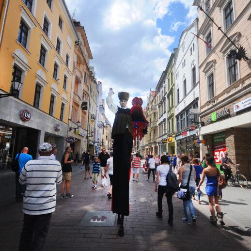 Odwołanie Końca Świata - szczudlasz pośrodku ulicy Szerokiej obwieszczający odwołanie końca świata