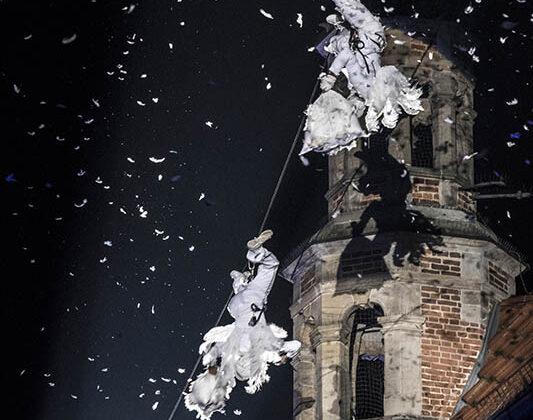 Plac Aniołów - dwóch artystów wstrojach aniołów zawieszonych do góry nogami na linie