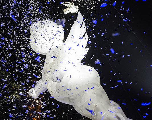 Plac Aniołów - balon wypełniony helem wkształcie anioła unosi się nad tłumem