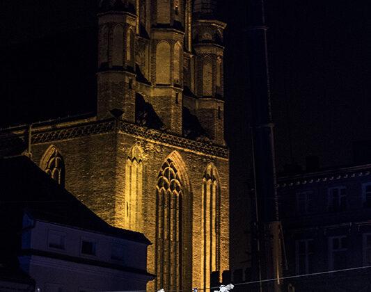 Plac Aniołów - artysta wstroju anioła zawieszony do góry nogami na tle kościoła