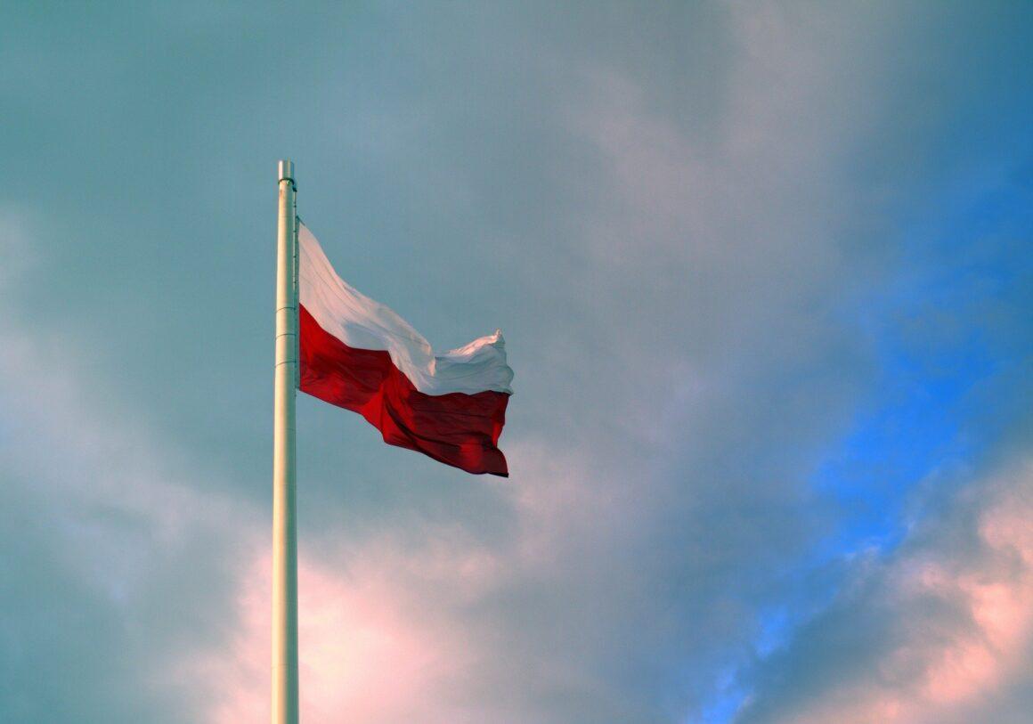 flaga Polski powiewająca na maszcie na tle nieba