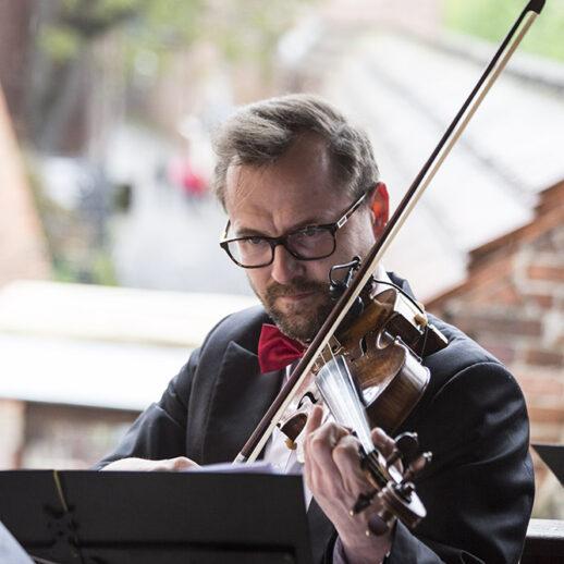 Zdjęcie przedstaiwa muzyka grającego na skrzypcach