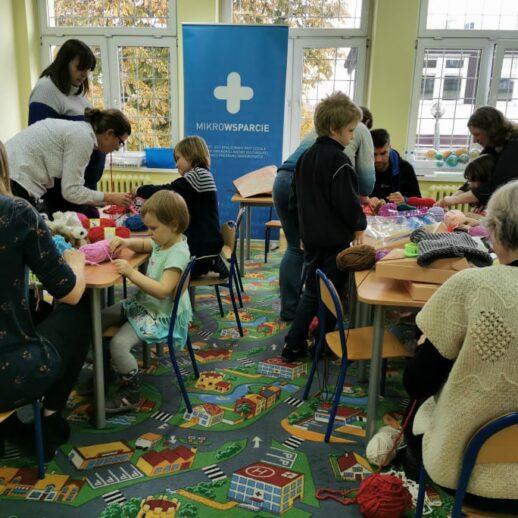dzieci idorośli siedzacy przy stołach podczas zajęć